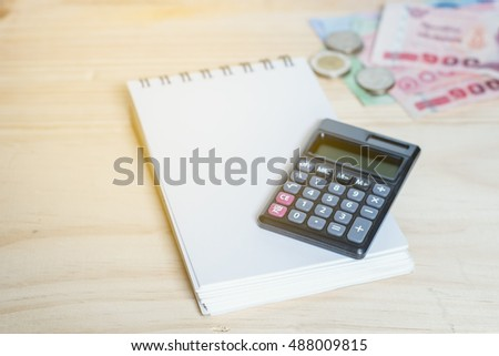 Calculator on note book with bill and coins background.
