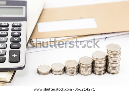 Calculator on notebook, pile of mail and coins on white background. - stock photo
