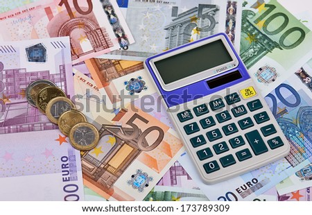 Calculator on the various euro banknotes and some coins. - stock photo