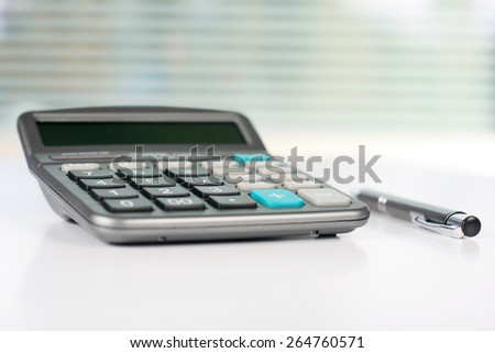 Calculator on white table in front of window. - stock photo