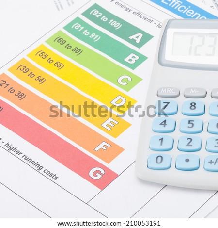 Calculator over energy efficiency chart - studio shot - 1 to 1 ratio - stock photo