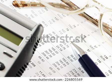 Calculator, pair of glasses and pen on a financial report. - stock photo
