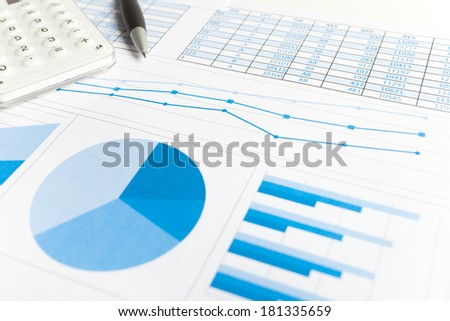 Calculator, pen and financial charts - stock photo