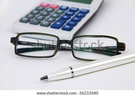 Calculator pen and glasses in isolated background - stock photo
