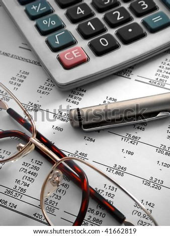 calculator, pen and glasses on financial statement - stock photo