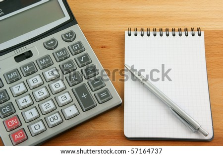 Calculator, pen and notebook on wooden table