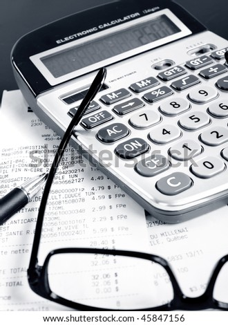 Calculator, pen, bills, receipt, eyeglasses on the table - stock photo