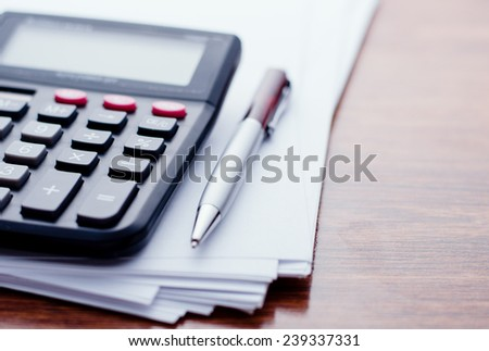 Calculator, pen, white paper for notes lie on the surface of a wooden table - stock photo