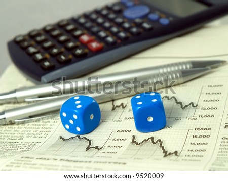 Calculator pens dice and financial pages of a newspaper. - stock photo