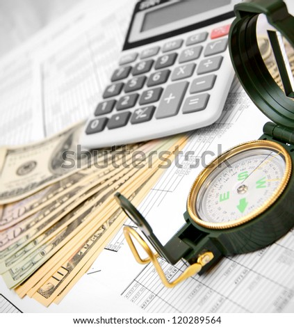 Calculator, roll of money and compass on documents.