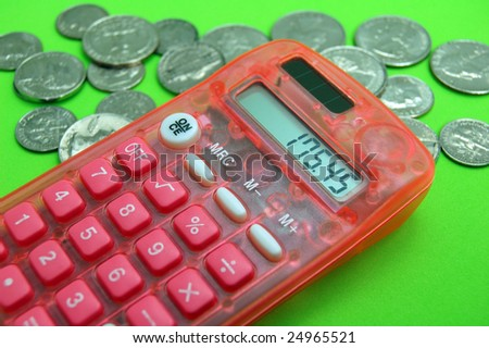 Calculator with coins on green background