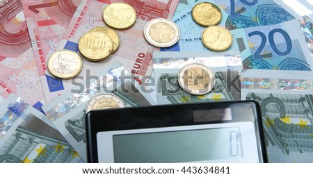 Calculator with Euro notes and coins. Finance concept. Closeup.