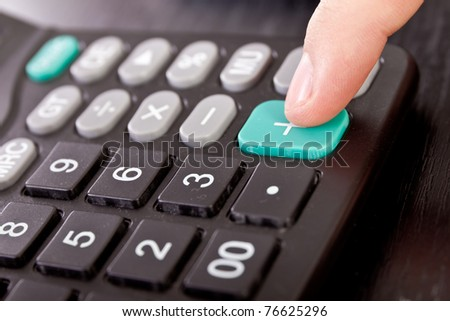 calculator with finger on button, close up - stock photo