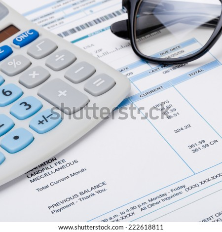 Calculator with glasses over receipt - 1 to 1 ratio - stock photo