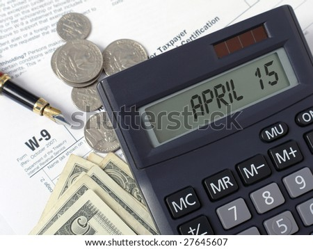 Calculator with lcd displaying April 15 placed on W-9 income tax forms with pen, and american dollars - stock photo