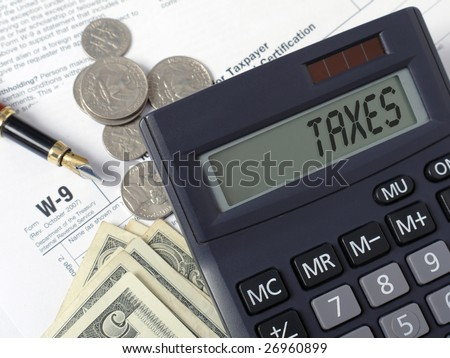 Calculator with lcd displaying Taxes word placed on W-9 income tax forms with pen, and american dollars - stock photo
