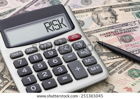 Calculator with money - Risk - stock photo