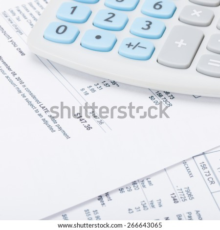 Calculator with monthly utility bill under it - close up shot - stock photo