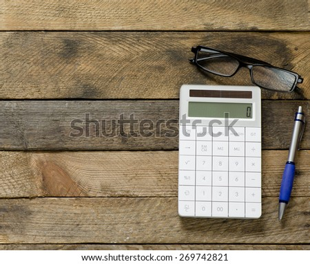 Calculator with notepad and glasses - stock photo