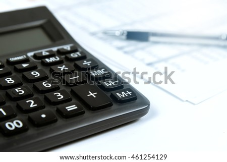 Calculator with pen and document in background with blue sunlight effect filter. Business concept