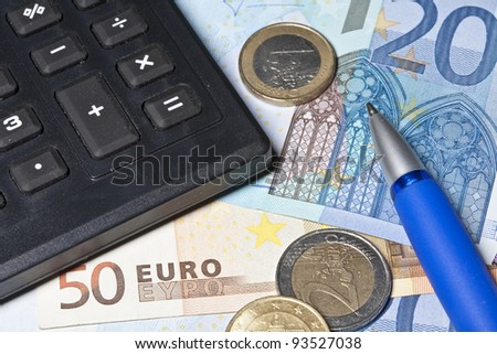 Calculator with pen and money - stock photo