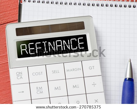 Calculator with refinance word. Calculator with refinance word and notepad, pen on background - stock photo