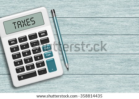 calculator with taxes text lying on wooden desk with place for text - stock photo