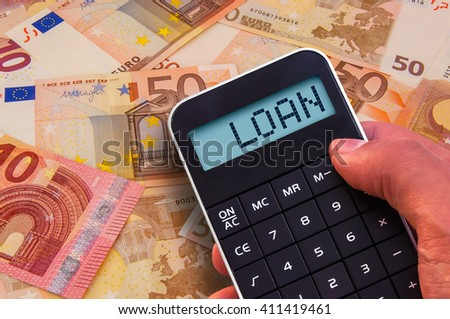 Calculator with the word Loan on the display and banknotes background - stock photo