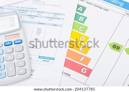 Calculator with utility bill and energy rating chart - stock photo