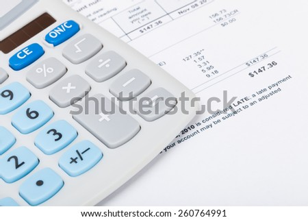 Calculator with utility bill under it - studio shot - stock photo