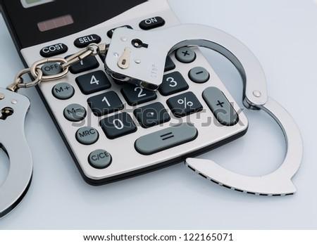 calculators and handcuffs on a white background. representative photo of white-collar crime - stock photo