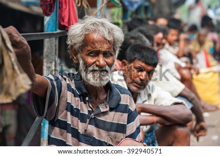 CALCUTTA - APRIL 13: Poor and jobless men waiting on the street for a job on April 13, 2014 in Calcutta, India. India has the largest number of people living below the poverty line of $1.25 per day. - stock photo