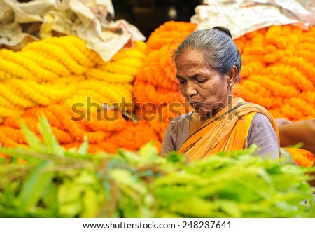 CALCUTTA - APRIL 13: woman selling flowers at the Howrah flower market on April 13, 2014 in Calcutta, India. Locals come here to buy flowers for worshiping their gods. - stock photo