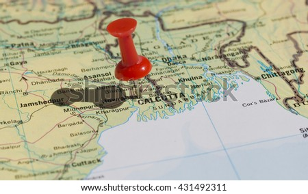 Calcutta marked on map with red pushpin. Selective focus on the word Calcutta and the pushpin. Pin is in an angle and casts some shadow to the left.  - stock photo