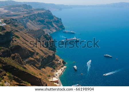 Caldera view on island of Santorini, Greece in Aegean sea with big and small commercial passenger ships. - stock photo