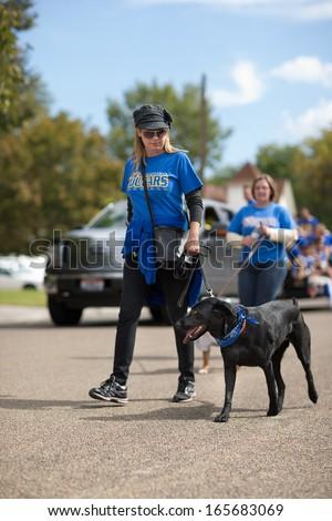 CALDWELL, IDAHO/USA - SEPTEMBER 27: Unidentified woman walks her dog through the Caldwell High School Homecoming parade on September 27, 2013  - stock photo