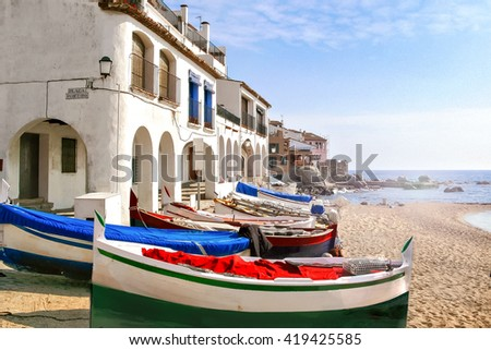 Calella de Palafrugell, Catalonia (Spain) - Traditional building with arches and fishing boats on the beach. - stock photo
