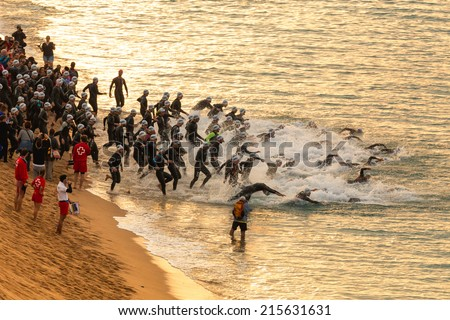 CALELLA - MAY 18: Triathletes on start of the Ironman triathlon competition at Calella beach, May 18, 2014 in Calella, Spain  - stock photo
