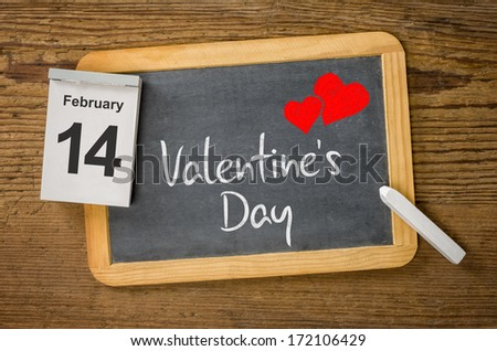 Calendar and blackboard showing February 14, Valentine's day  - stock photo
