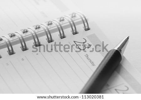 Calendar and pen closeup photo in an office desk. - stock photo