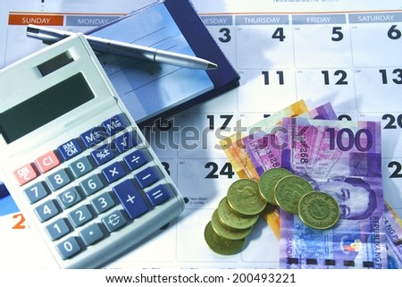 Calendar, checkbook, calculator, money and a ballpen Photo of a calendar, checkbook, calculator, money and a ballpen - stock photo
