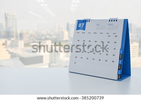Calendar of July on the white table with city view background - stock photo