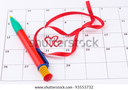Calendar page with hearts, pen and ribbon on St.Valentines Day - stock photo