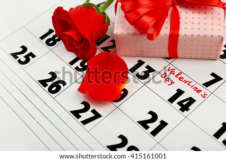 Calendar with date of February 14, gift box and rose flower petals. Valentines day concept