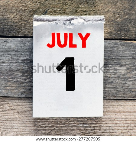 Calendar with 1 july on wooden background - stock photo