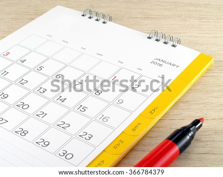 calendar with red marker pen on wooden table background - stock photo
