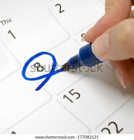 Calendars are drawn circle at 8 with a blue pen. - stock photo