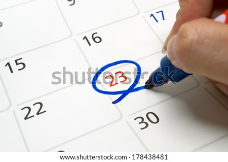 Calendars are drawn circle at 23 with a blue pen. - stock photo