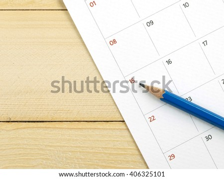 calender and pencil on wood background