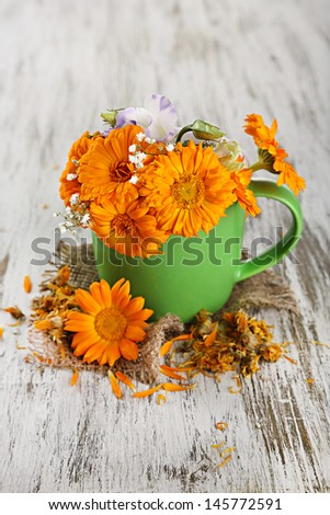 Calendula flowers in cup on wooden background - stock photo